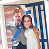 Harry and Meghan lookalikes in front of a blue and pink beach hut