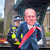 A man wearing a Prince Philip mask, being arrested by a police officer, underneath the Tyne Bridge