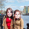 Two girls wearing masks of the princesses with the Quayside in the background