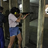 A girl firing a gun a shooting range