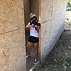 A girl hiding, whilst firing a gun