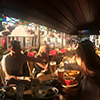 A group of people eating and drinking outside