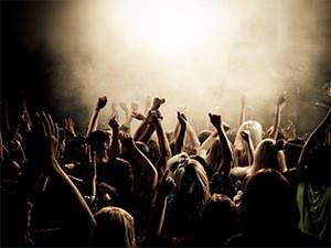 People dancing in a club with their hands in the air to a smoky backdrop