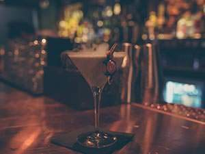 A cocktail in a martini glass, with a sweet on the rim, on a bar counter
