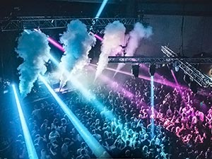 People in a club to a backdrop of blue and pink light, and smoke