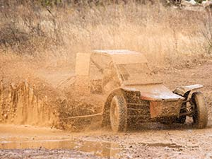 A rage buggy covered in mud and in a muddy field