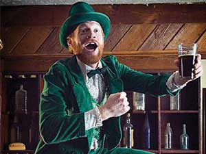 A cheery Irish man dressed in a green suit, holding a pint of Guinness
