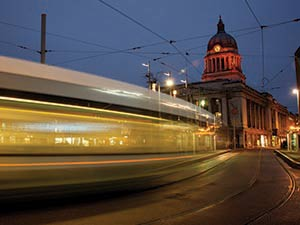 A tram passing a building in Nottingham, with the long exposure capturing all of the lights