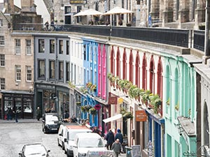 A line of colourful buildings on a cobbled street, in Grassmarket