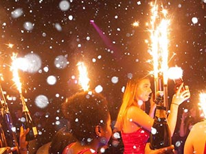 Women in a club holding champagne bottles with sparklers in
