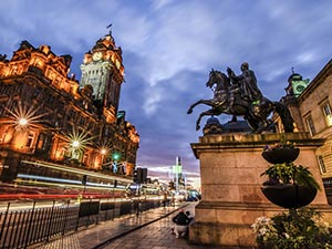 A monument of a man riding a horse and a grand building in Edinburgh