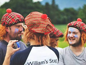 Three people in Scottish hats, whilst one man paints another man's face
