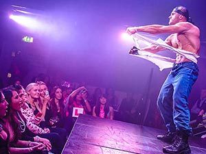A man ripping his shirt off on stage, to a crowd of women