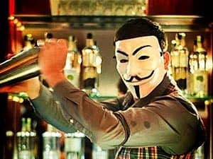 A bartender in an Anonymous mask, shaking a cocktail shaker