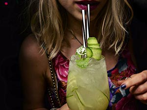 A girl drinking from two straws in a cucumber cocktail