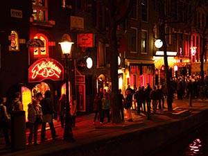 People stood in the streets in the Amsterdam Red Light District, at night