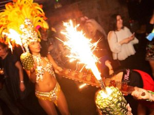 An oriental looking woman wearing feathers and carrying a tray of shots, with a sparkler coming out of a pineapple in the foreground