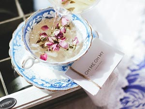 A cup of tea in a porcelain mug, with flower heads in and a business card on the side