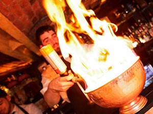 A barman carrying a bowl of cocktail which is set alight