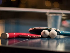Two ping pong bats along with a ball, set up on a table