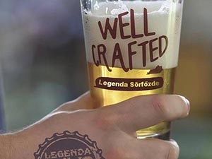 A person's hand holding a beer with 'Well Crafted' written on