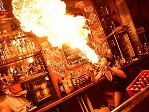 A girl blowing fire behind a bar