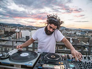 A man with curly hair doing the DJ decks on Bar 360 in Budapest