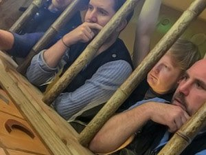 Four men looking through bamboo bars at a puzzle