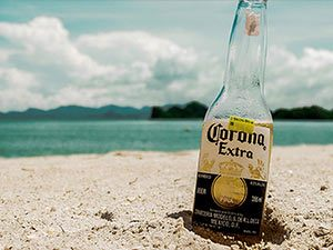 A Corona bottle in the sand, with the sea out of focus behind it