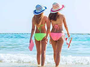 Two women in bikinis, facing the sea