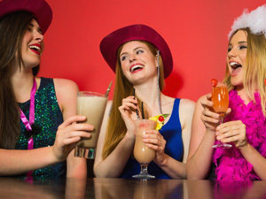 Three girls having fun and drinking cocktails on a hen do