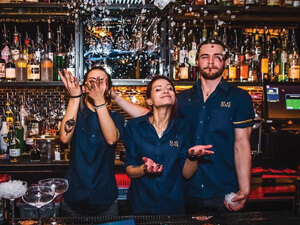 Three bartenders behind a bar