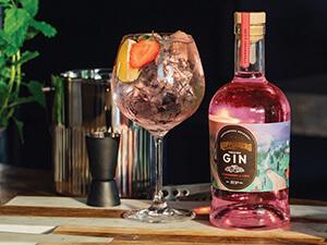 A close up of a bottle of gin and a glass on a table