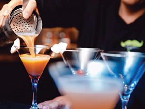 A close up of a bartender making a drink