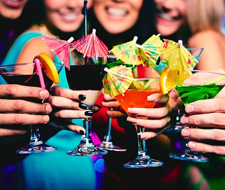 Some girls holding their martini glasses in front of them, with tiny umbrellas in