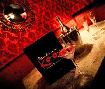 A reserved table at Madame Koo, topped with champagne and a cocktail