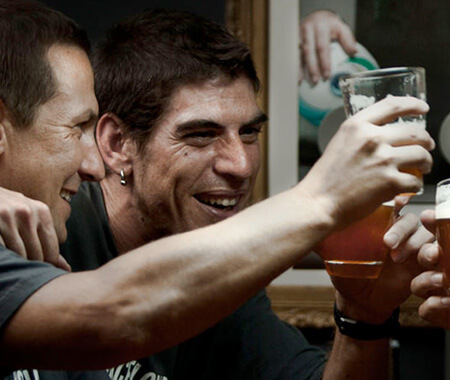A group of men holding up beers in a pub in Barcelona
