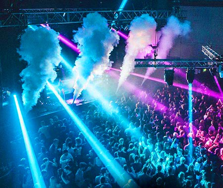 Blue and pink strobe lights, along with smoke, over a crowd of people in a club