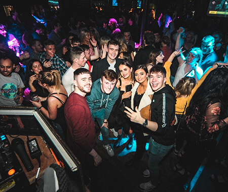 A group of men and women dancing in a nightclub
