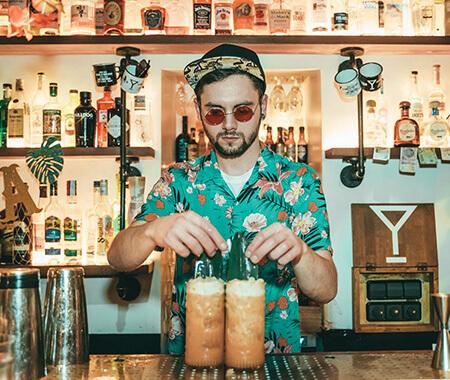 A bartender serving drinks behind a bar
