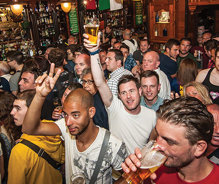A group of men celebrating in a pub