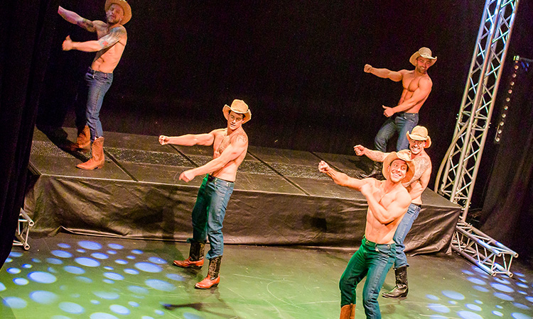 Four semi-naked men dressed as cowboys, dancing on stage