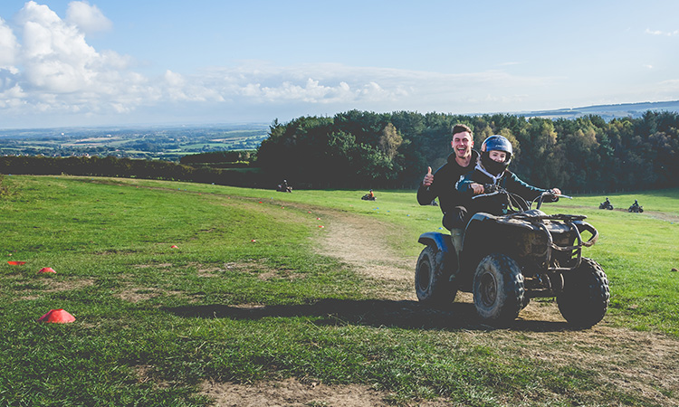 A girl riding a quad bike with an instructor on the back