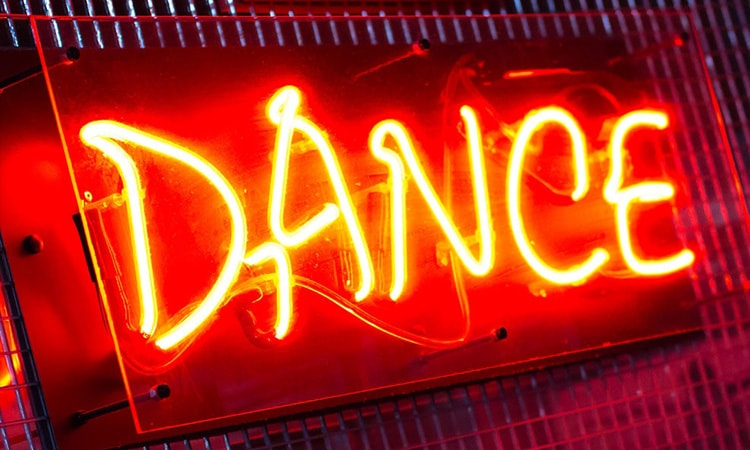 Lit up red Dance sign against a wall