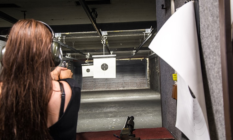 The back of a woman firing a pistol at a target, in a shooting range