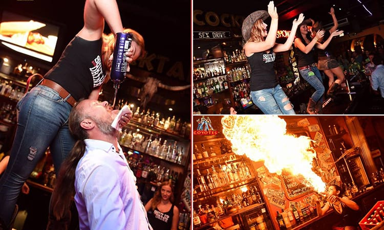 A man having alcohol poured into his mouth, girls dancing on the bar and a girl blowing fire