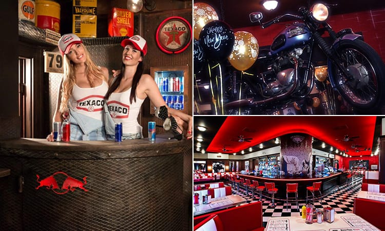 Two girls dressed in caps and vests behind the bar, a motorcycle on the wall and an American style diner