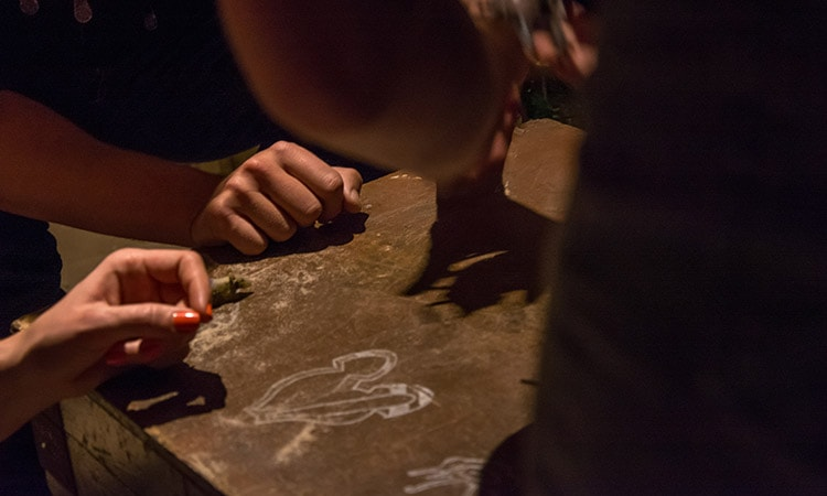 Some peoples' hands on a box with chalked drawings on