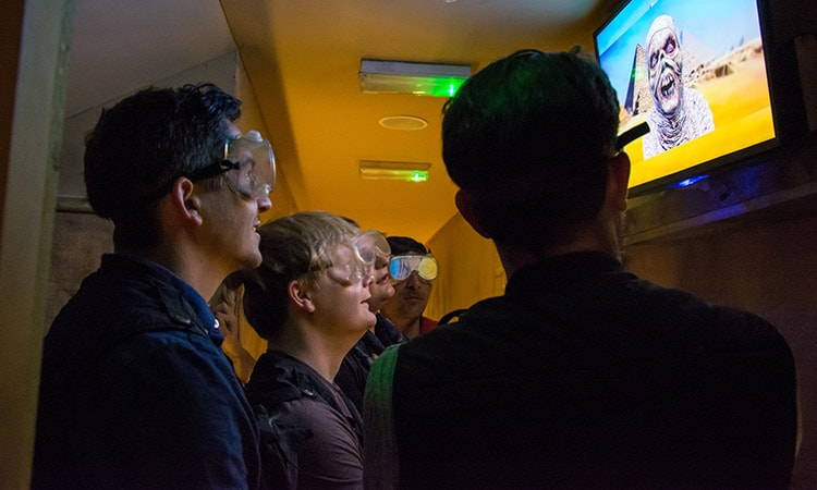 LNOF team members wearing goggles and looking up at an image of a mummy on the screen