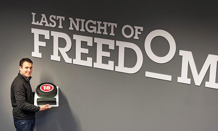 Matt holding the LNOF 18 cake against the logo on the wall